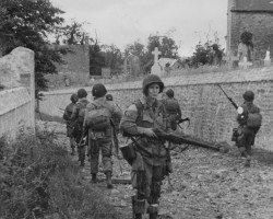 Paratroopers pass through a village churchyard, Normandy