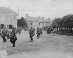 Paratroopers pass through Ste. Marie-du-Mont enroute to Carentan